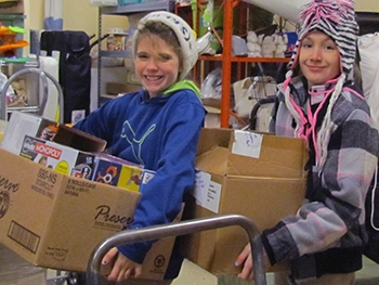 Students from Douglas MacArthur Elementary School carry toys into the Family Support Center.